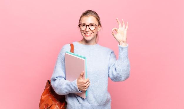 Młoda ładna studentka czuje się szczęśliwa, zrelaksowana i usatysfakcjonowana, okazując aprobatę dobrym gestem, uśmiechając się