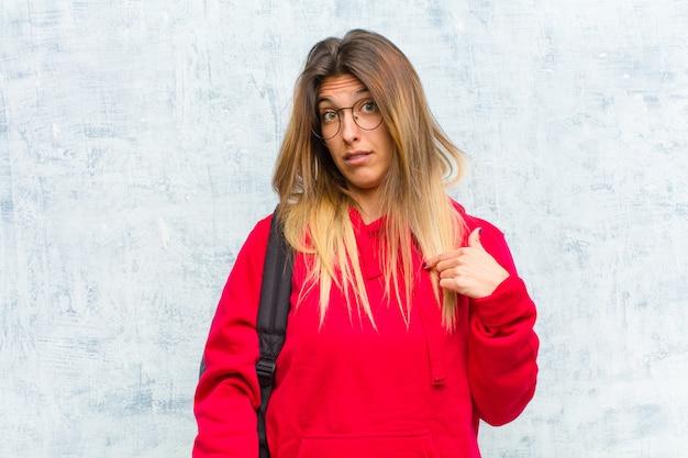 Młoda ładna studentka czuje się zdezorientowana, zdziwiona i niepewna, wskazując na siebie, zastanawiając się i pytając, kto, ja?
