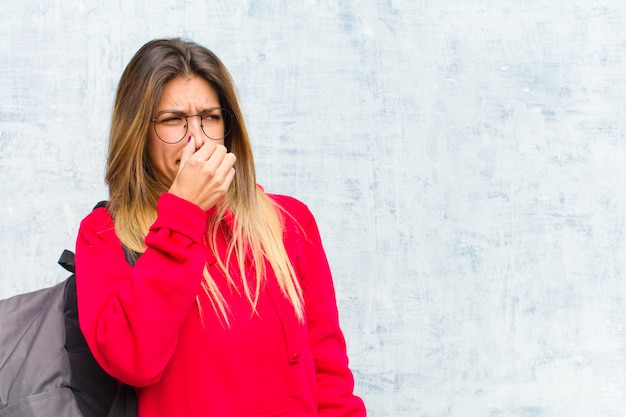 Młoda ładna studentka czuje się zniesmaczona, trzymając nos, aby nie poczuć nieprzyjemnego i nieprzyjemnego smrodu