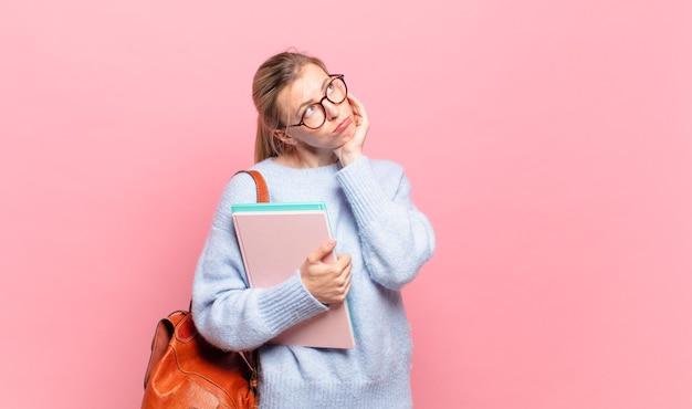 Młoda ładna studentka czuje się znudzona, sfrustrowana i senna po męczącym, nudnym i żmudnym zadaniu, trzymając twarz ręką