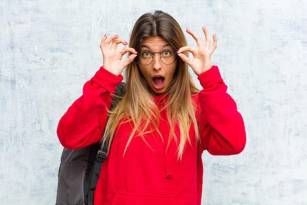 Młoda ładna studentka czuje się zszokowana, zdziwiona i zaskoczona, trzymając okulary ze zdziwieniem i niedowierzaniem