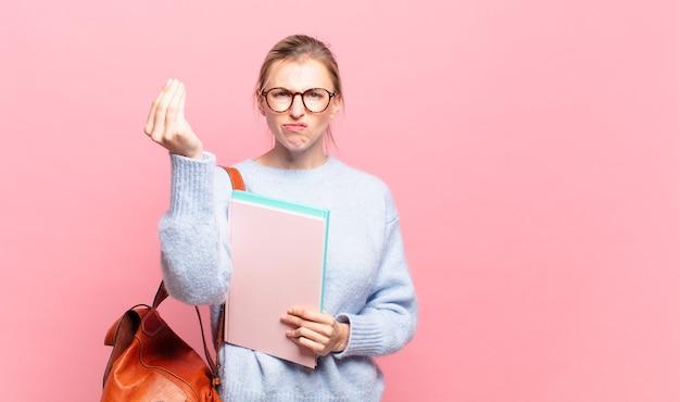 Młoda ładna studentka robi gest kaprysu lub pieniędzy, każąc spłacić długi!