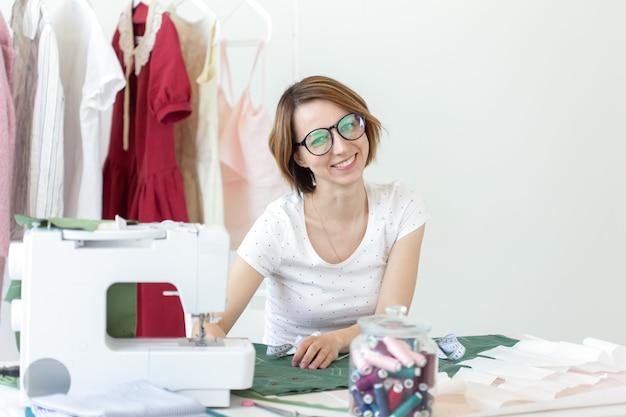 Młoda ładna studentka studiuje u projektanta ubrań w college'u i robi swoją pierwszą pracę magisterską siedząc przy biurku z maszyną do szycia. koncepcja projektowania odzieży.