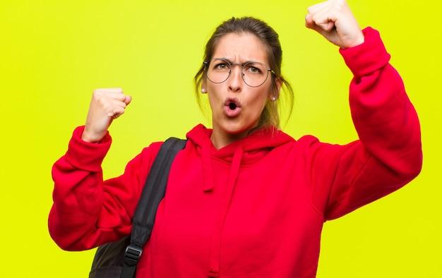Młoda ładna studentka świętuje niewiarygodny sukces jak zwycięzca, wyglądając na podekscytowaną i radosną mówiąc: weź to!