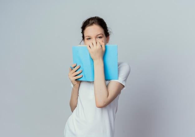 Młoda ładna studentka trzymając otwartą książkę i pióro i patrząc na kamery z tyłu książki na białym tle na białym tle z miejsca kopiowania