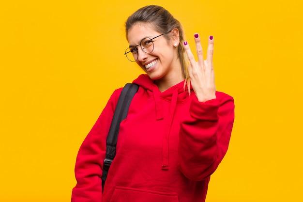 Młoda ładna studentka uśmiechnięta i wyglądająca przyjaźnie, pokazując numer trzy lub trzeci ręką do przodu, odliczając