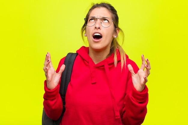 Młoda ładna studentka wściekle krzyczy, czując się zestresowana i zirytowana rękami w powietrzu, mówiąc mi, dlaczego ja