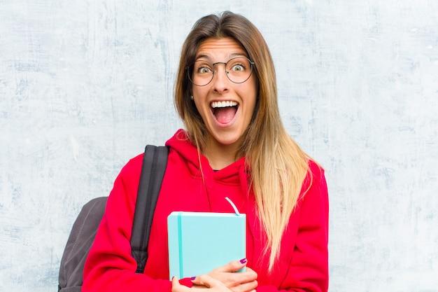 Młoda ładna studentka wygląda na szczęśliwą i mile zaskoczoną, podekscytowaną zafascynowanym i zszokowanym wyrazem twarzy