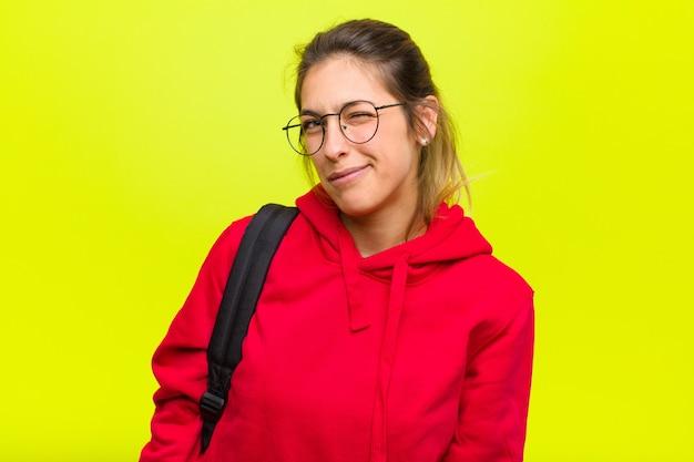 Młoda ładna studentka wygląda na szczęśliwą i przyjazną, uśmiecha się i mruga do ciebie z pozytywnym nastawieniem