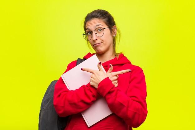 Młoda ładna studentka wygląda na zdziwioną i zdezorientowaną, niepewną i z wątpliwościami wskazuje w przeciwnych kierunkach