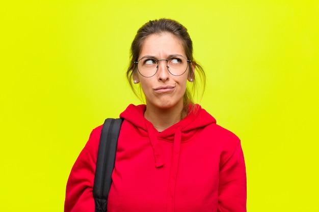 Młoda ładna studentka wygląda na zdziwioną i zdezorientowaną, zastanawiając się lub próbując rozwiązać problem lub myśleć