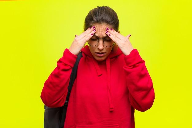 Młoda ładna studentka wygląda na zestresowaną i sfrustrowaną, pracując pod presją z bólem głowy i niepokojąc się problemami