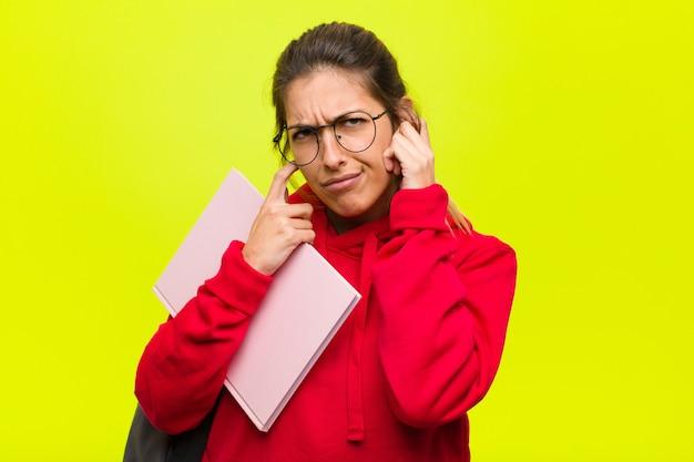 Młoda ładna studentka wygląda na złą, zestresowaną i zirytowaną, zakrywającą uszy ogłuszającym hałasem, dźwiękiem lub głośną muzyką