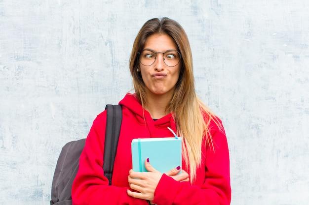 Młoda ładna studentka wyglądająca na głupkowatą i zabawną z głupim zezem, żartująca i wygłupiana