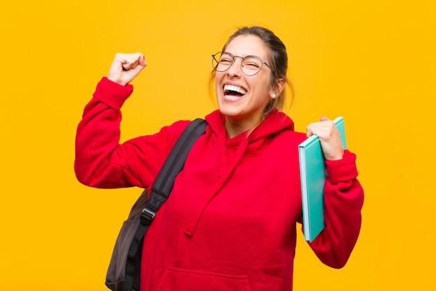 Młoda ładna studentka wyglądająca na wyjątkowo szczęśliwą i zaskoczoną świętuje sukces krzycząc i skacząc