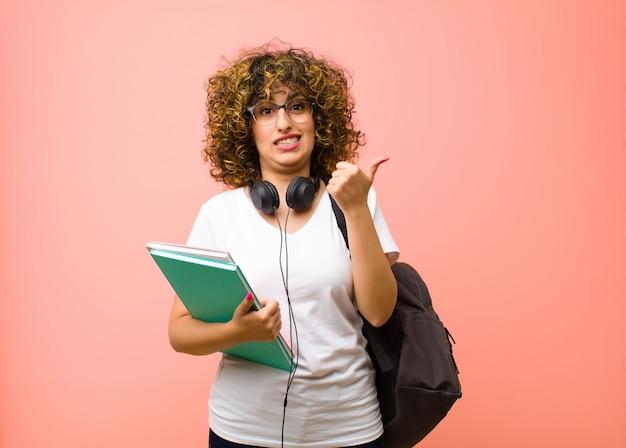 Młoda ładna studentka wyglądająca na zdziwioną i zdezorientowaną, niepewną i wskazującą w przeciwnych kierunkach z wątpliwościami na różowej ścianie