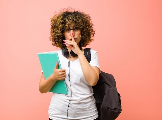Młoda ładna studentka wyglądająca poważnie i krzyżująca z palcem przyciśniętym do ust, domagająca się ciszy lub spokoju, trzymająca sekret nad różową ścianą