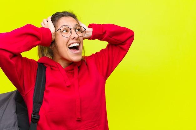 Młoda ładna studentka z otwartymi ustami, wyglądająca na przerażoną i zszokowaną z powodu strasznego błędu, podnosząca ręce do głowy