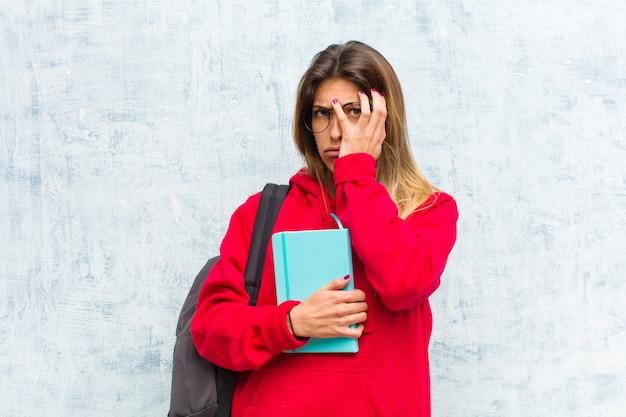 Młoda ładna studentka znudzona, sfrustrowana i senna po męczącym, nudnym i żmudnym zadaniu, trzymając twarz ręką