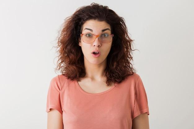 Młoda ładna stylowa kobieta w okularach, kręcone włosy, zszokowany, zdziwiony wyraz twarzy, śmieszne emocje, na białym tle, różowa koszulka