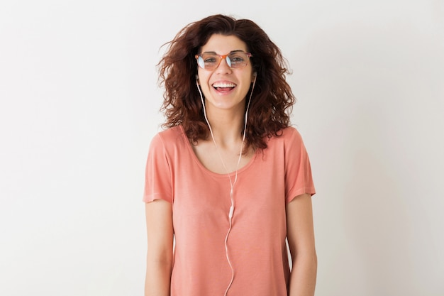 Młoda ładna stylowa kobieta w okularach, słuchanie muzyki na słuchawkach, kręcone włosy, śmiech, pozytywne szczere emocje, szczęśliwa, odizolowana, różowa koszulka