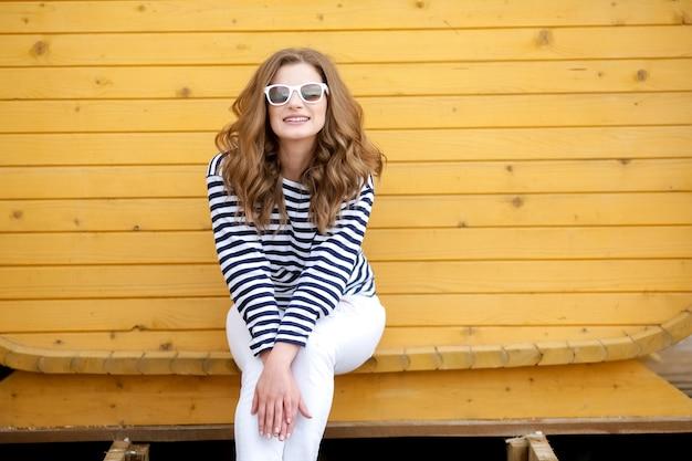 Młoda ładna stylowa uśmiechnięta kobieta robi selfie zdjęciu w aparacie w parku miejskim, pozytywna, emocjonalna, ubrana w żółty top, różowe okulary przeciwsłoneczne, trend mody w stylu lata, długie włosy, całowanie