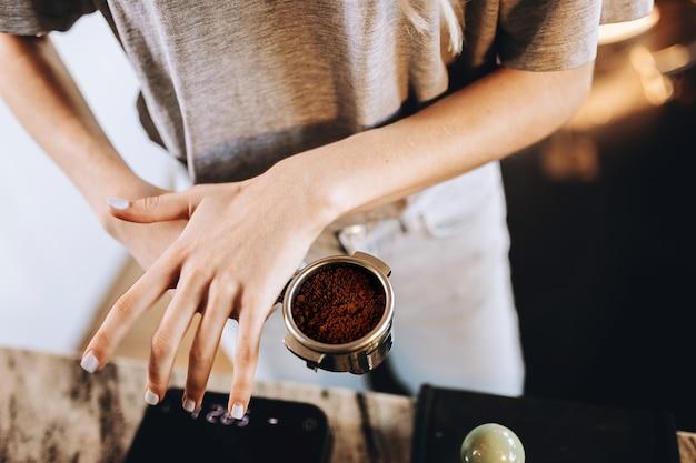Młoda, ładna, szczupła dziewczyna, ubrana w swobodny strój, gotuje kawę w nowoczesnej kawiarni. koncentruje się na procesie. .