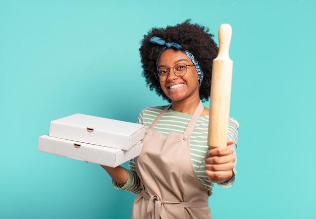 Młoda ładna szefowa kuchni afro z wałkiem do ciasta i pizzą