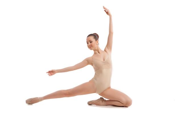 Młoda ładna tancerka baletowa siedzi w eleganckiej pozie na białym tle