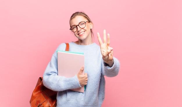 Młoda ładna uczennica uśmiechnięta i wyglądająca przyjaźnie, pokazująca numer trzy lub trzeci z ręką do przodu, odliczając w dół