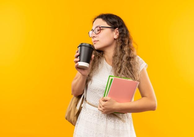 Młoda ładna uczennica w okularach i plecaku trzyma książkę i notes i wącha filiżankę kawy z zamkniętymi oczami na białym tle na żółtym tle z miejsca na kopię