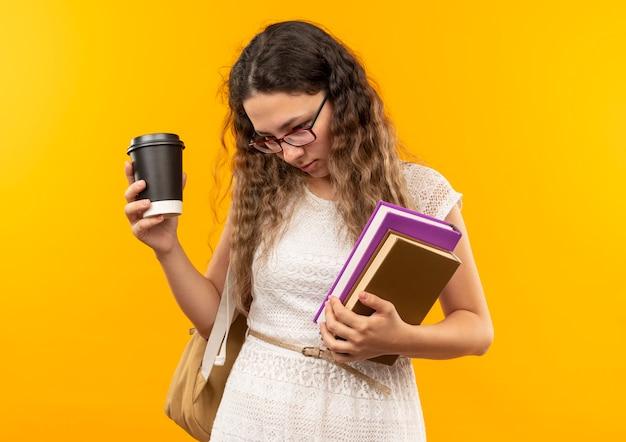 Młoda ładna uczennica w okularach iz powrotem trzyma plastikową filiżankę kawy i książki patrząc w dół na białym tle na żółtym tle z miejsca na kopię