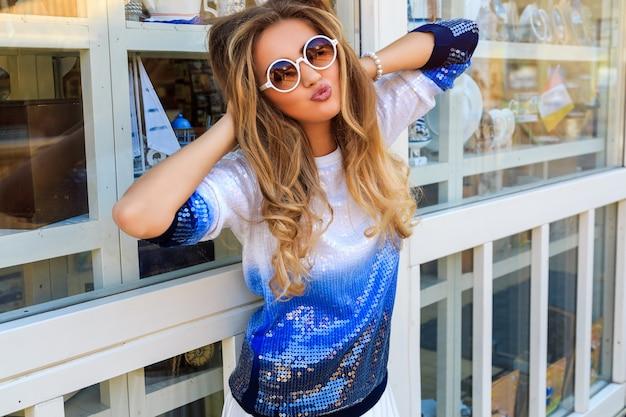 Młoda ładna uśmiechnięta dziewczyna pozuje w pobliżu sklepu z pamiątkami z łodziami i żeglarskimi towarami, ma na sobie ombre sweter, ma naturalny makijaż i puszystą kręconą fryzurę. miłego dnia i miłych zakupów.