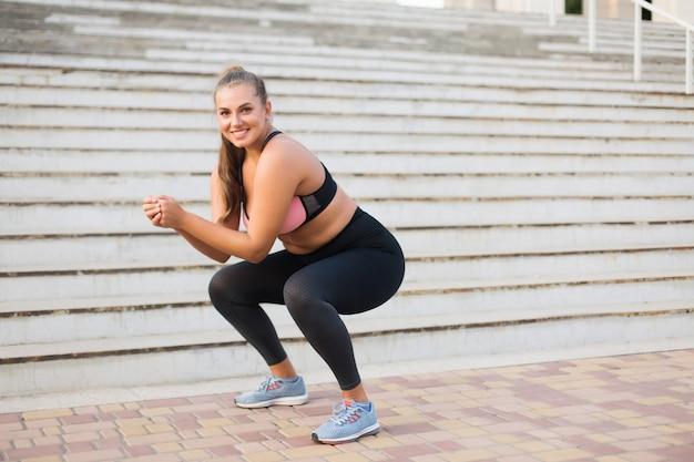 Młoda ładna uśmiechnięta kobieta plus size w sportowy top i legginsy uprawia sport ze schodami