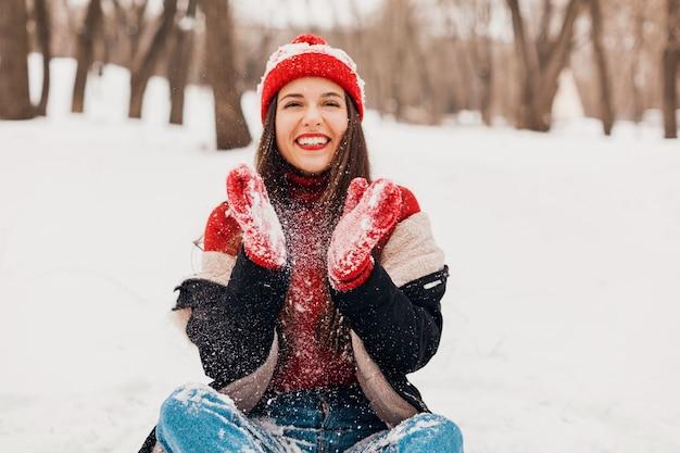 Młoda ładna uśmiechnięta szczęśliwa kobieta w czerwonych rękawiczkach i czapce na sobie płaszcz zimowy siedzi na śniegu w parku, ciepłe ubrania