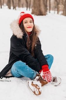 Młoda ładna uśmiechnięta szczęśliwa kobieta w czerwonych rękawiczkach i czapce w zimowym płaszczu, spacerująca w parku, bawiąca się śniegiem w ciepłych ubraniach