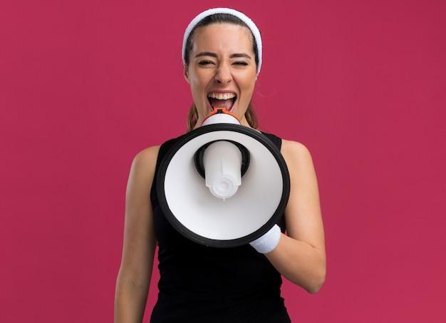 Młoda ładna wysportowana dziewczyna nosząca opaskę i opaski na nadgarstki krzycząca w głośnym głośniku