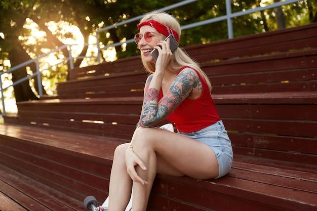 Młoda ładnie roześmiana blondynka z wytatuowanymi ramionami, rozmawiająca ze swoim przyjacielem na smartfonie, ubrana w czerwoną koszulkę, dżinsowe szorty, z dzianinową bandaną na głowie, w czerwonych okularach.