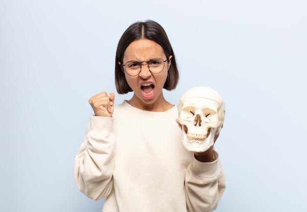 Młoda latynoska, agresywnie krzycząca z gniewnym wyrazem twarzy lub zaciśniętymi pięściami, świętuje sukces