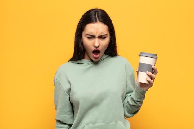 Młoda latynoska agresywnie krzyczy, wygląda na bardzo wściekłą, sfrustrowaną, oburzoną lub zirytowaną, krzycząc nie