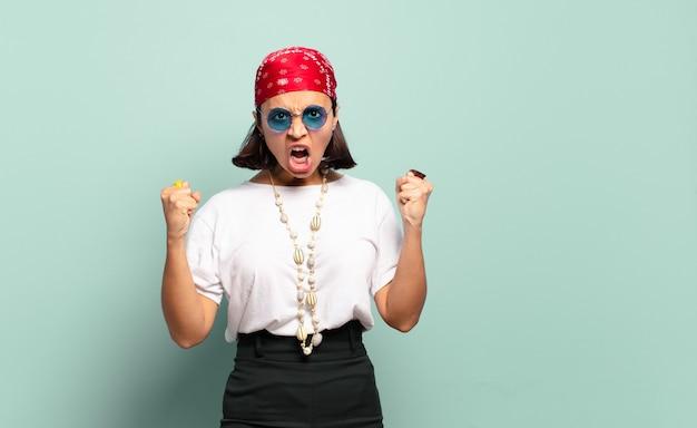 Młoda latynoska agresywnie krzyczy z gniewnym wyrazem twarzy lub z zaciśniętymi pięściami świętując sukces