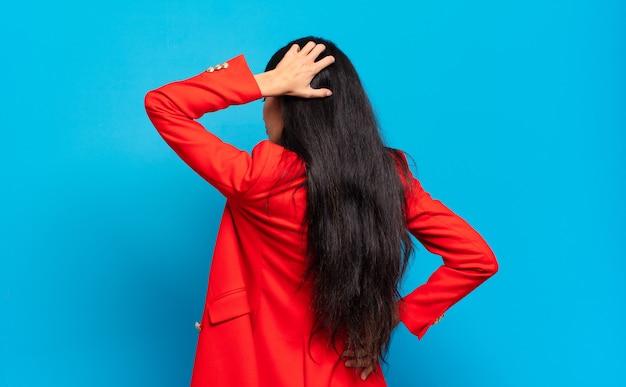 Młoda latynoska bizneswoman czuje się nieświadoma i zdezorientowana, myśląc o rozwiązaniu, z ręką na biodrze i drugą na głowie, widok z tyłu