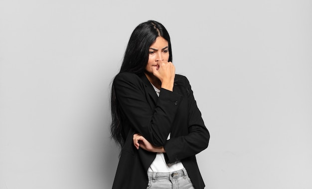 Młoda latynoska bizneswoman czuje się poważna, zamyślona i zatroskana, wpatrzona w bok z ręką przyciśniętą do brody