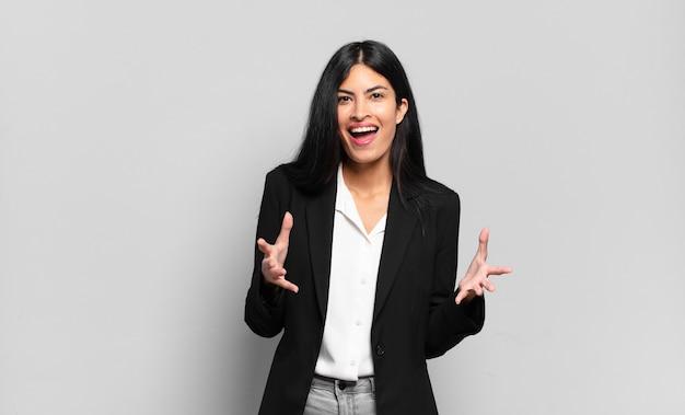 Młoda latynoska bizneswoman czuje się szczęśliwa, zdziwiona, szczęśliwa i zaskoczona, mówiąc poważnie omg? nie do wiary