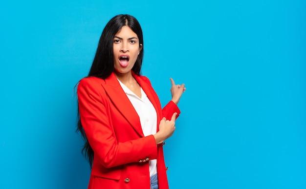 Młoda latynoska bizneswoman czuje się zszokowana i zaskoczona, wskazując na skopiowanie miejsca z boku ze zdumieniem i otwartymi ustami