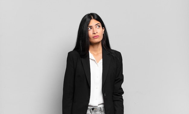 Młoda latynoska bizneswoman o zmartwionej, zdezorientowanej, nieświadomej twarzy, patrząca w górę, by skopiować przestrzeń, wątpiąca