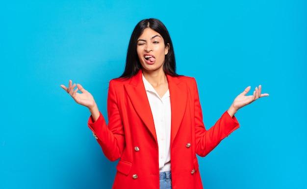 Młoda latynoska bizneswoman wzrusza ramionami z głupim, szalonym, zdezorientowanym, zdziwionym wyrazem twarzy, czuje się zirytowana i nieświadoma