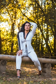 Młoda latynoska brunetka w bardzo eleganckim białym garniturze w czarne paski. moda pozowała w pięknym parku na siedząco