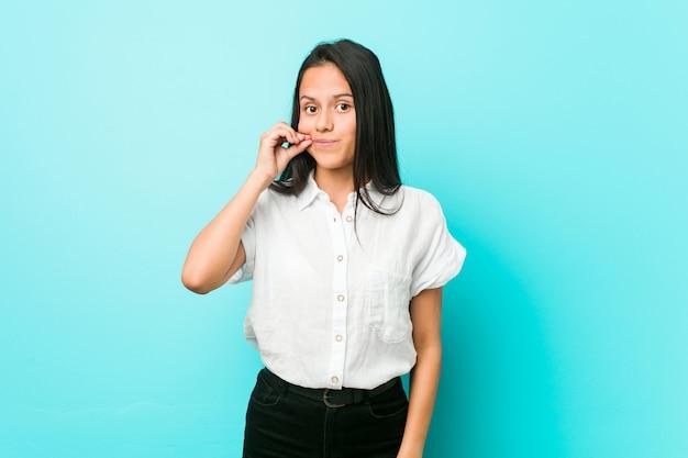 Młoda latynoska chłodna kobieta o niebieską ścianę z palcami na ustach utrzymująca sekret.