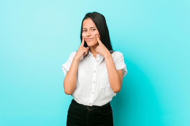 Młoda latynoska chłodna kobieta o niebieskiej ścianie, wątpiąca w dwie opcje.